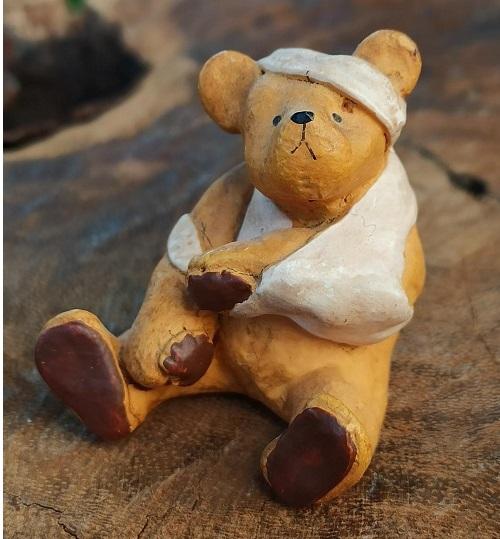 Sötaste lilla björn som skadat sig både i huvudet och i armen. Handmålad och levereras i en vacker papperskartong med sidenband.