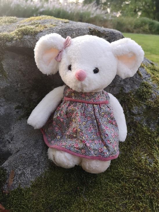Vit nalle i blommig klänning med grå botten och rosa små blommor. Rosa rosett vid örat och rosa nos från Bukowski Design