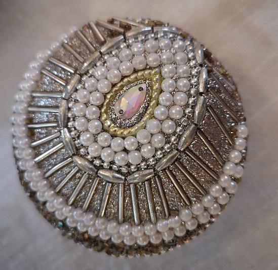 Rund ask i guld med vita glaspärlor till förvaring av medicin, pengar eller smycken.