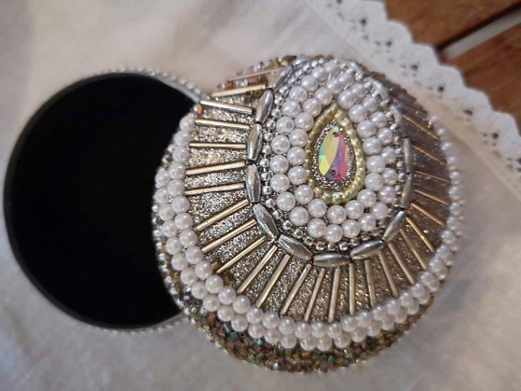 Rund ask i guld med svartvita glaspärlor till förvaring av medicin, pengar eller smycken.