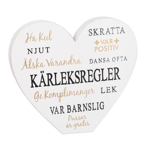 ett vitt hjärta i trä med ord som ha kul, skratta, njut, älska varandra, var barnslig, pussar är gratis m.m. från different design