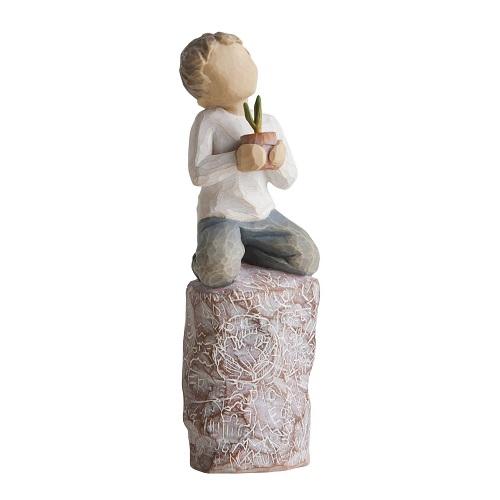 Something special från Willow Tree. En pojke sitter på en mönstrad stubbe med en krukväxt i händerna.
