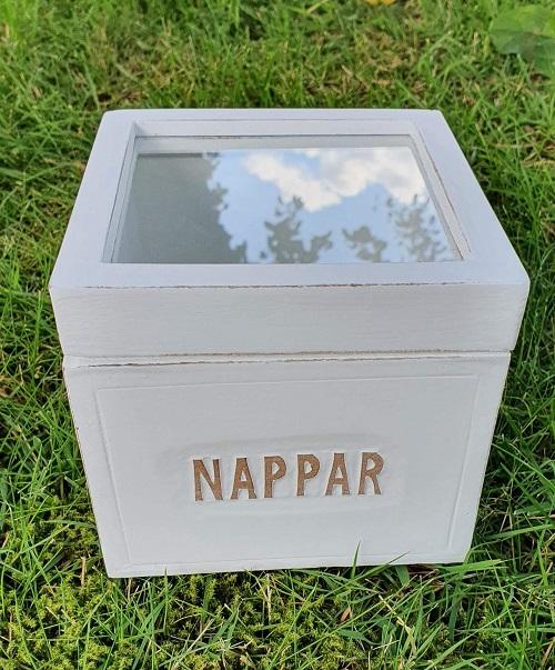 Vit träask med text Nappar och locket är med en ram av trä och glas från Different Design