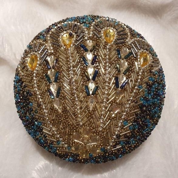 större förvaringsask som är rund i guld och blågröna nyanser i vackert mönster.